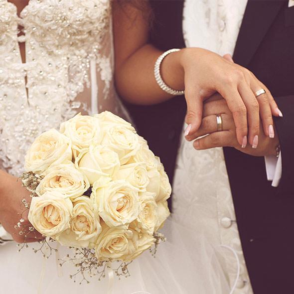 Ein frisch verheiratetes Ehepaar hält sich die Hände, zeigt die RInge und einen Strauß